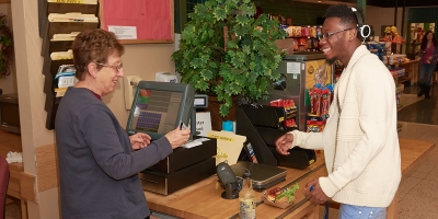 A student hands his ID card to a cashier in High Acres food court at Penn State Hazleton.