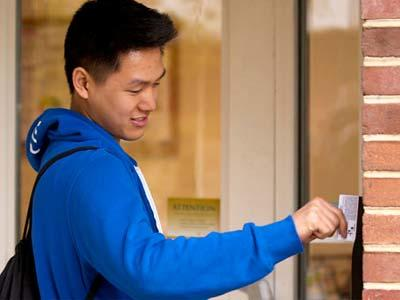 A student swipes his id card to enter his Penn State residence Hall.